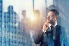 El hombre de negocios piensa nuevas estrategias para crecer la compañía Exposición doble imagen de archivo