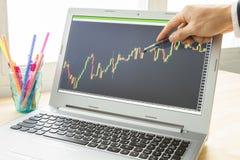 El hombre de negocios Point y analiza el gráfico de las divisas o el gráfico de la acción por uso Imagenes de archivo
