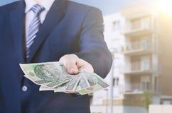El hombre de negocios polaco sostiene el dinero El préstamo en la casa Fotos de archivo