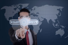 El hombre de negocios presiona la tecla de partida con 2017 Foto de archivo