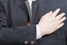 El hombre de negocios presiona su mano al corazón - gesto de mano Fotos de archivo