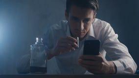 El hombre de negocios presionado vierte el whisky en un vaso de medida que bebe solamente en un cuarto oscuro Concepto de alcohol metrajes