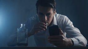 El hombre de negocios presionado vierte el whisky en un vaso de medida que bebe solamente en un cuarto oscuro Concepto de alcohol almacen de video