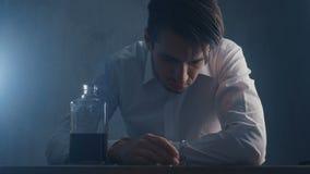 El hombre de negocios presionado vierte el whisky en un vaso de medida que bebe solamente en un cuarto oscuro Concepto de alcohol almacen de metraje de vídeo