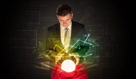 El hombre de negocios previó el futuro del mercado de acción con una bola mágica Imágenes de archivo libres de regalías