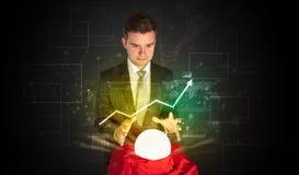 El hombre de negocios previó el futuro del mercado de acción con una bola mágica Foto de archivo