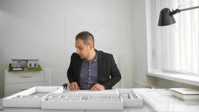 El hombre de negocios proyecta arquitectura con el interfaz aumentado de la realidad almacen de video