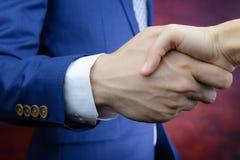 El hombre de negocios que alcanza la mano, sacude las manos, acuerdo del trato Fotografía de archivo libre de regalías