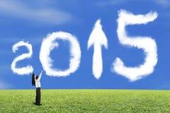 El hombre de negocios que anima la flecha 2015 encima de la forma se nubla con la hierba del cielo Fotos de archivo libres de regalías