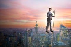 El hombre de negocios que camina en los zancos - colocándose hacia fuera de la muchedumbre fotografía de archivo