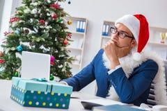 El hombre de negocios que celebra día de fiesta de la Navidad en la oficina Foto de archivo