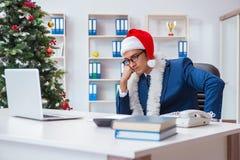 El hombre de negocios que celebra día de fiesta de la Navidad en la oficina Imagen de archivo libre de regalías