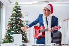El hombre de negocios que celebra día de fiesta de la Navidad en la oficina Imágenes de archivo libres de regalías