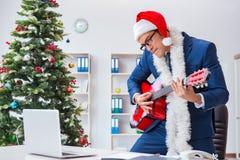 El hombre de negocios que celebra día de fiesta de la Navidad en la oficina Imagenes de archivo