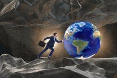 El hombre de negocios que empuja el mundo en concepto del desafío Foto de archivo
