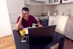 El hombre de negocios que hace cuenta sobre costos en casa, el presupuesto familiar y finanzas, calcula sus cuentas, planeando el fotos de archivo