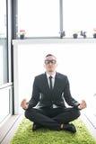 El hombre de negocios que hace yoga en verde carpen en lavabo de la oficina Foto de archivo libre de regalías