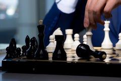 El hombre de negocios que juega a ajedrez en concepto de la estrategia Imagenes de archivo