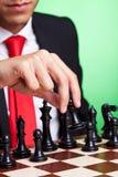 El hombre de negocios que juega negro del ajedrez hace el primer movimiento Imágenes de archivo libres de regalías