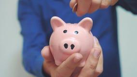 El hombre de negocios que la forma de vida hace ahorros pone monedas en una hucha Concepto del negocio de la hucha vídeo de la cá almacen de metraje de vídeo