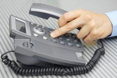 El hombre de negocios que la mano está marcando un número de teléfono con cogido dirige Foto de archivo libre de regalías