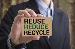 El hombre de negocios que lleva a cabo el mensaje del businesscard recicla, reduce, reutiliza Fotografía de archivo libre de regalías