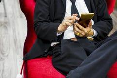 El hombre de negocios que lleva un traje negro que se sienta en una silla roja del terciopelo, smartphone de la pantalla táctil,  fotografía de archivo libre de regalías