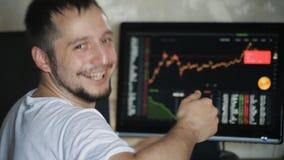 El hombre de negocios que mira las estadísticas de sus ganancias y las demostraciones manosean con los dedos para arriba metrajes