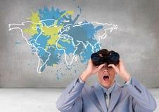 El hombre de negocios que miraba a través de los prismáticos con el mapa colorido con la pintura salpicó el fondo de la pared Foto de archivo