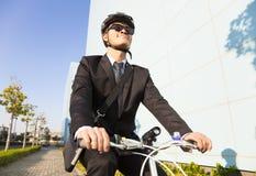 El hombre de negocios que monta una bicicleta al lugar de trabajo para proteger rodea Fotografía de archivo