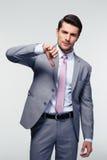 El hombre de negocios que muestra el pulgar abajo firma Imagen de archivo libre de regalías