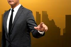 El hombre de negocios que muestra la mano y el finger con la ciudad se enciende en backgrou Fotos de archivo libres de regalías