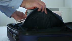 El hombre de negocios que prepara la ropa del equipaje y del control enumera con la tableta electr?nica almacen de metraje de vídeo
