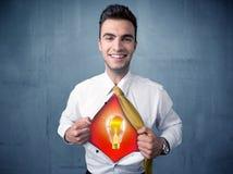 El hombre de negocios que rasga de la camisa y de la bombilla de la idea aparece Imágenes de archivo libres de regalías