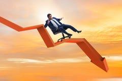 El hombre de negocios que resbala abajo en silla en concepto de la crisis económica Imagen de archivo
