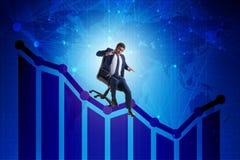 El hombre de negocios que resbala abajo en silla en concepto de la crisis económica Foto de archivo