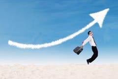 El hombre de negocios que salta bajo muestra de la flecha del beneficio Imagenes de archivo