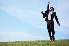 El hombre de negocios que salta en hierba Imagenes de archivo