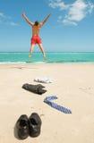 El hombre de negocios que salta en la playa Fotografía de archivo
