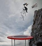 El hombre de negocios que salta en un trampolín para alcanzar la bandera Meta de negocio del logro y concepto difícil de la carre fotos de archivo libres de regalías