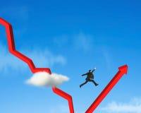 El hombre de negocios que salta sobre gowing abajo de flecha roja Imagen de archivo
