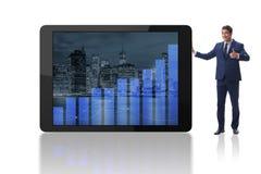 El hombre de negocios que se coloca al lado de la tableta en el fondo blanco fotografía de archivo libre de regalías