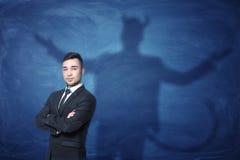 El hombre de negocios que se coloca con las manos a través y su sombra en la pizarra azul detrás de él cola les gusta el diablo Fotografía de archivo