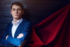 El hombre de negocios que se coloca en un traje y la capa roja les gusta el super héroe Foto de archivo libre de regalías