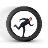 El hombre de negocios que se reclamará por tiempo está corriendo en el centro de una rueda grande foto de archivo
