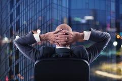 El hombre de negocios que se relaja en oficina y piensa en el futuro Exposición doble foto de archivo