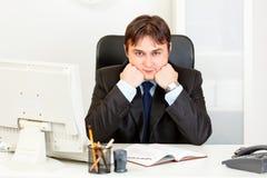 El hombre de negocios que se sienta en el escritorio y el mantiene dirigen en las manos fotos de archivo