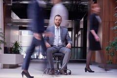 El hombre de negocios que se sienta en silla de la oficina, gente agrupa el paso cerca Imagenes de archivo