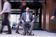 El hombre de negocios que se sienta en silla de la oficina, gente agrupa el paso cerca Imagen de archivo libre de regalías
