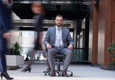El hombre de negocios que se sienta en silla de la oficina, gente agrupa el paso cerca Fotografía de archivo libre de regalías